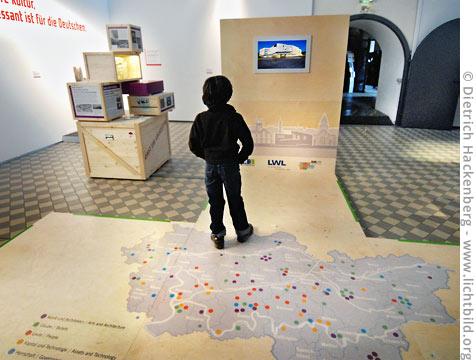 """Wanderausstellung """"Fremde Impulse"""". Karte mit Bildschirm und eine von sechs Installationen. © Dietrich Hackenberg"""