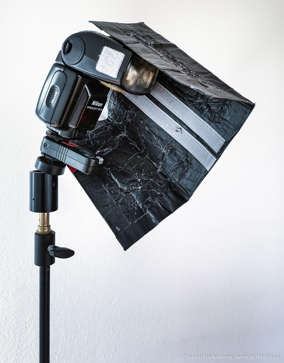 Blitzgerät mit Funkzelle und Black-Wrap-Blende, die mit Klettband flexibel befestigt werden kann.  Black-Wrap ist eine schwarz beschichtete, formbare Metallfolie aus dem Filmlichtbereich. Ich nutze diese um das Licht der Blitzgeräte zu formen oder unerwünschtes Streulicht abzuschirmen.