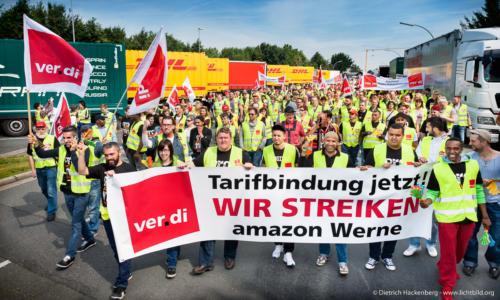 Amazon Streikzug vorbei an den LKW der Anlieferung. Foto Dietrich Hackenberg