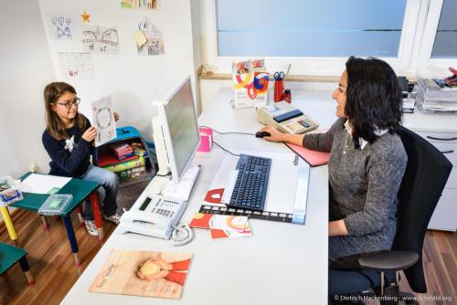 """Die ehemalige Teilzeitauszubildende hat ihre kranke ältere Tochter mit ins Büro genommen. Eine Kinderecke ist im Büro vorhanden. NRW Landesprogramm """"Teilzeitberufsausbildung"""". Foto Dietrich Hackenberg – www.lichtbild.org"""